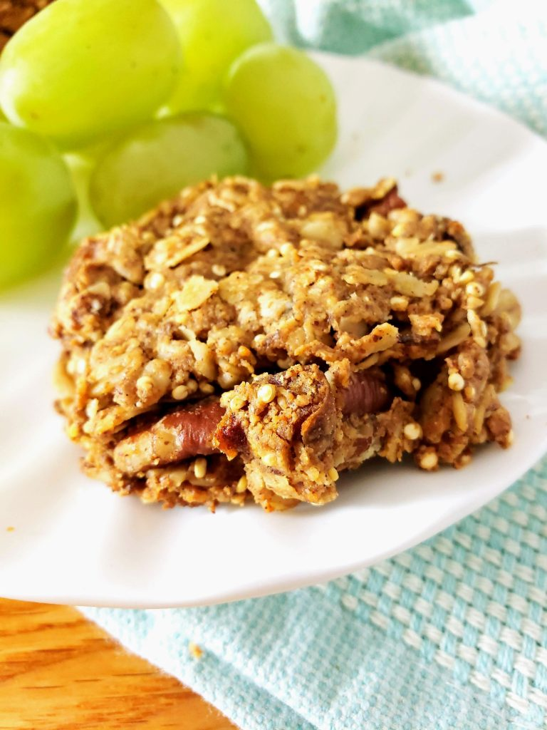 one gluten free healthy breakfast cookie on a white plate with grapes behind it