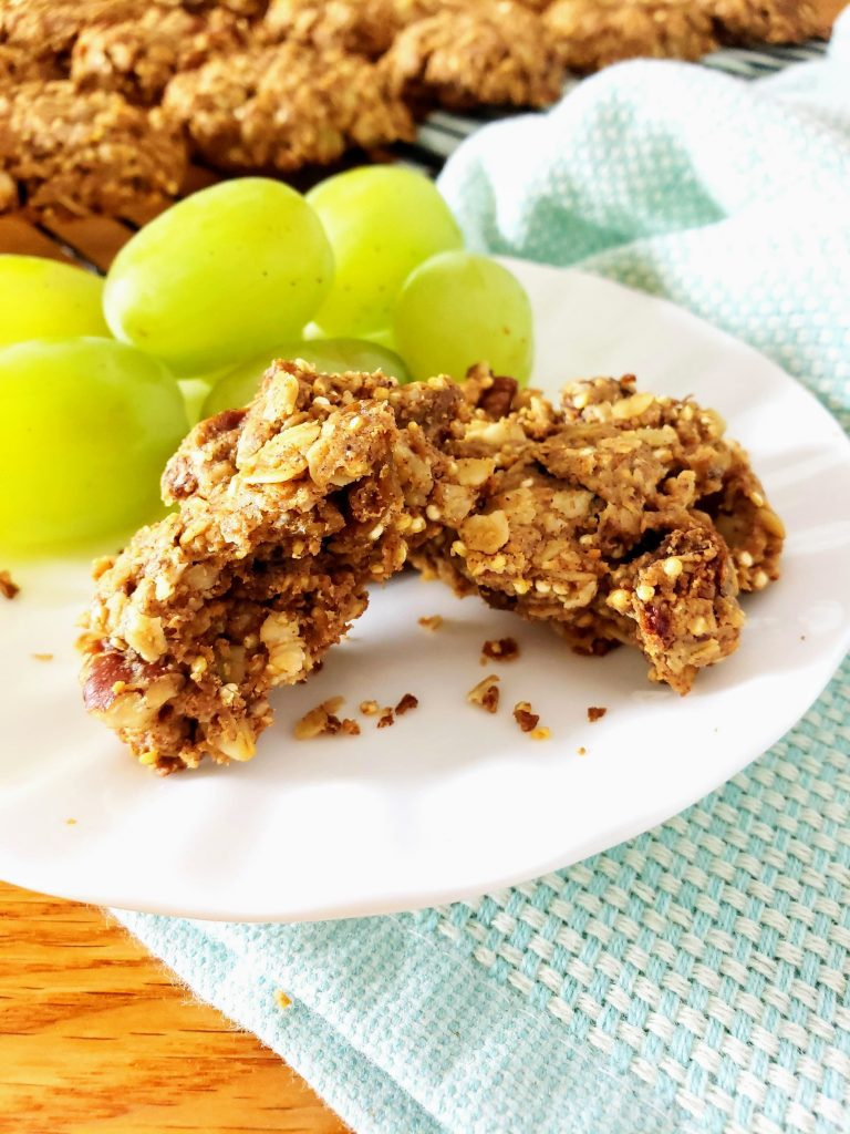 gluten free healthy breakfast cookie broken in half on a white plate with grapes behind it