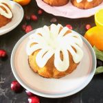 mini cranberry orange bundt cake on a plate with two cakes behind it