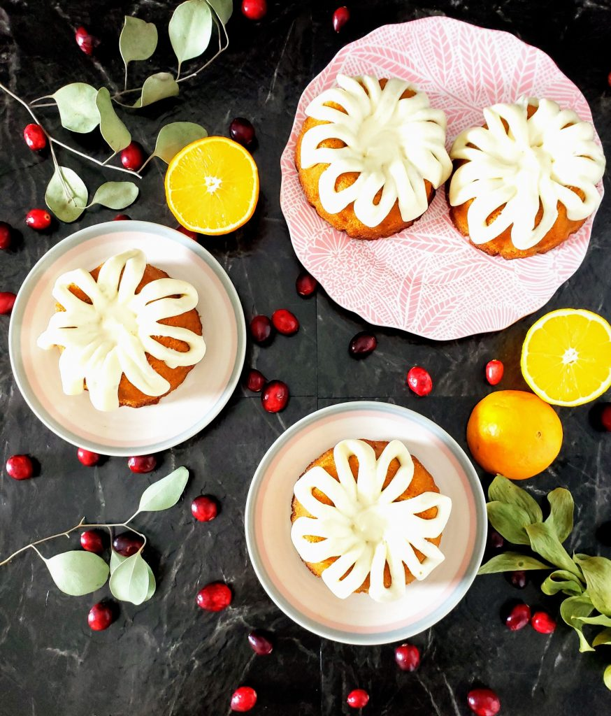 top down view of four mini cranberry orange bundt cakes {two on one plate, two separate plates with one on each}