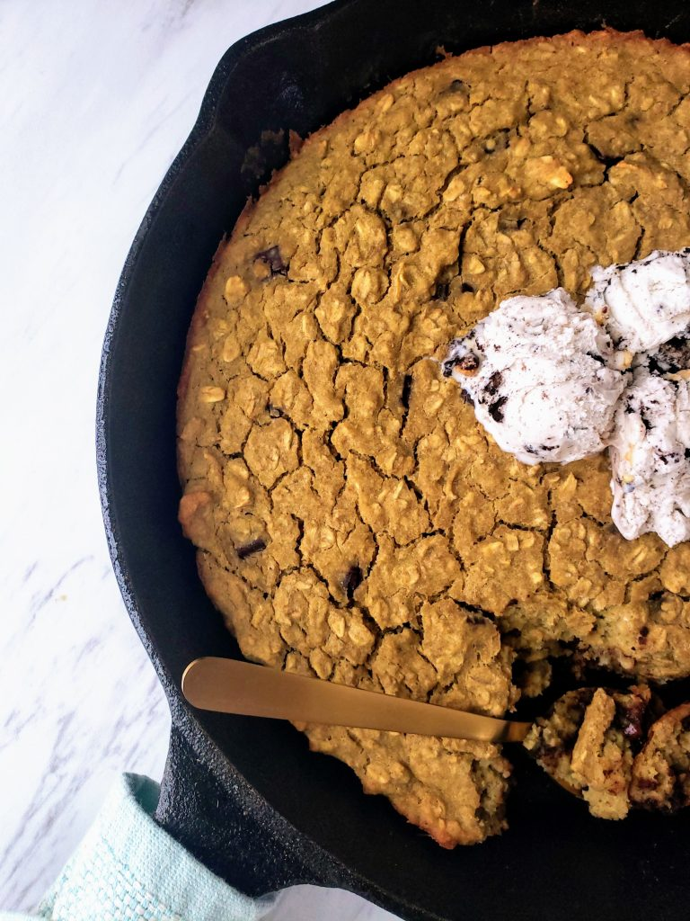 healthy oatmeal chocolate chip skillet cookie with a spoon in the pan and ice cream on top