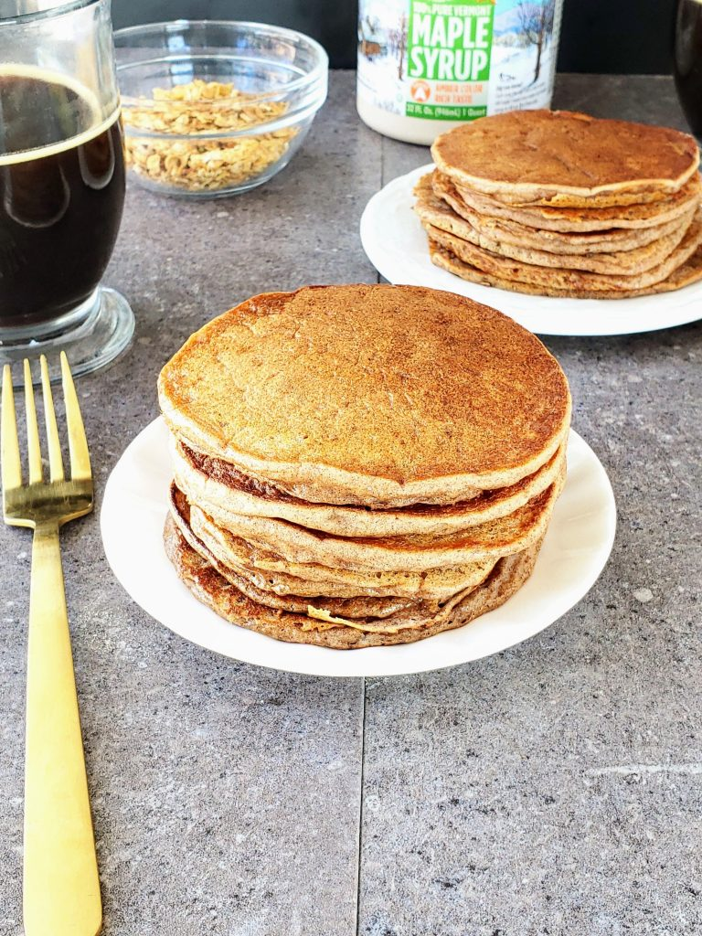stacks of cinnamon ricotta pancakes on two plates with coffee and cereal in the background