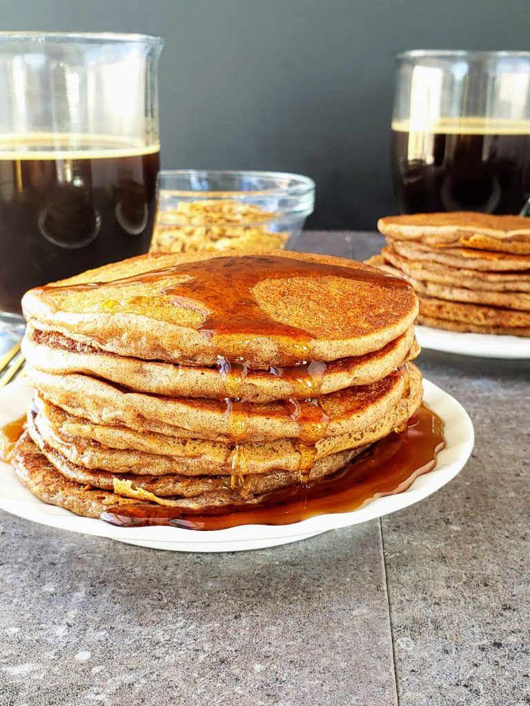 stack of cinnamon ricotta pancakes with syrup dripping down the side