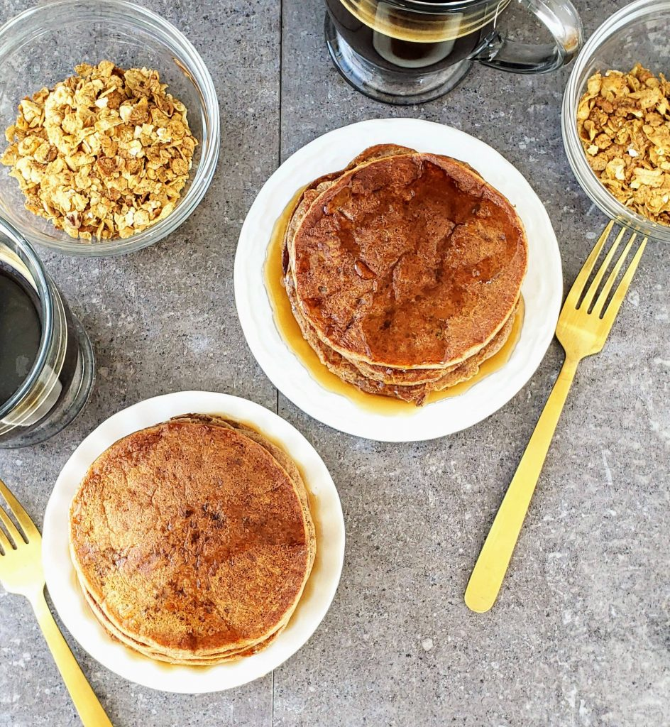 stacks of cinnamon ricotta pancakes on two white plates with cereal in bowls and mugs of coffee