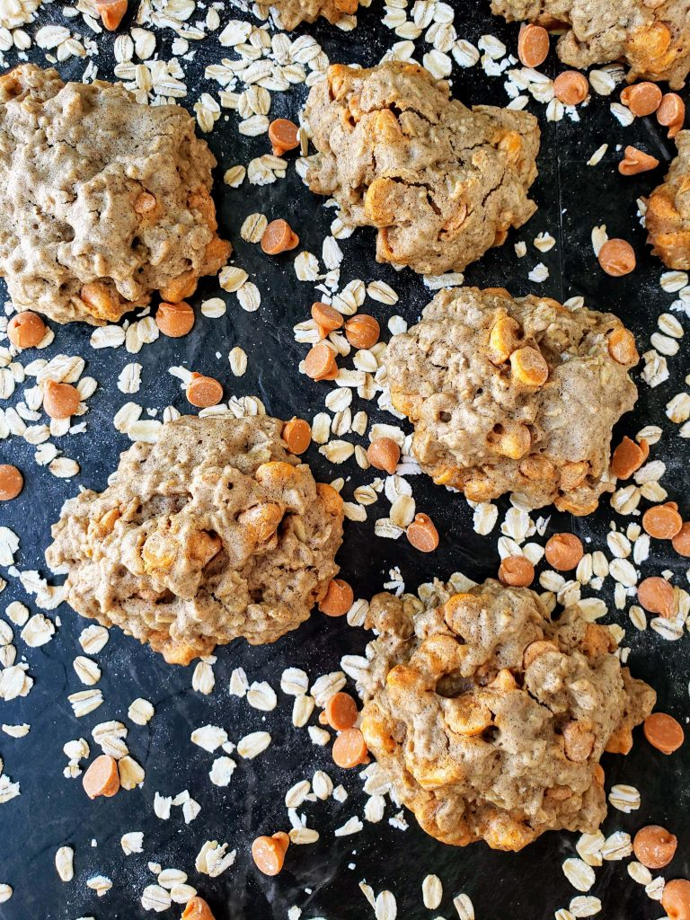 bourbon caramel oatmeal cookies surrounded by oats and caramel chips