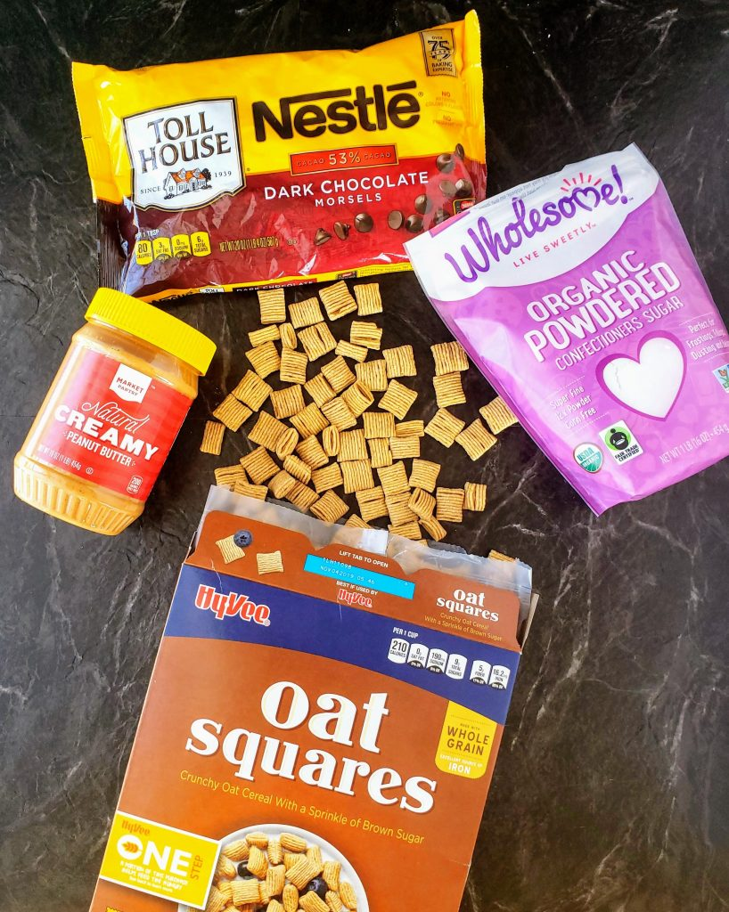 box of oat squares cereal spilled on a table surrounded by a peanut butter jar, bag of dark chocolate chips and powdered sugar