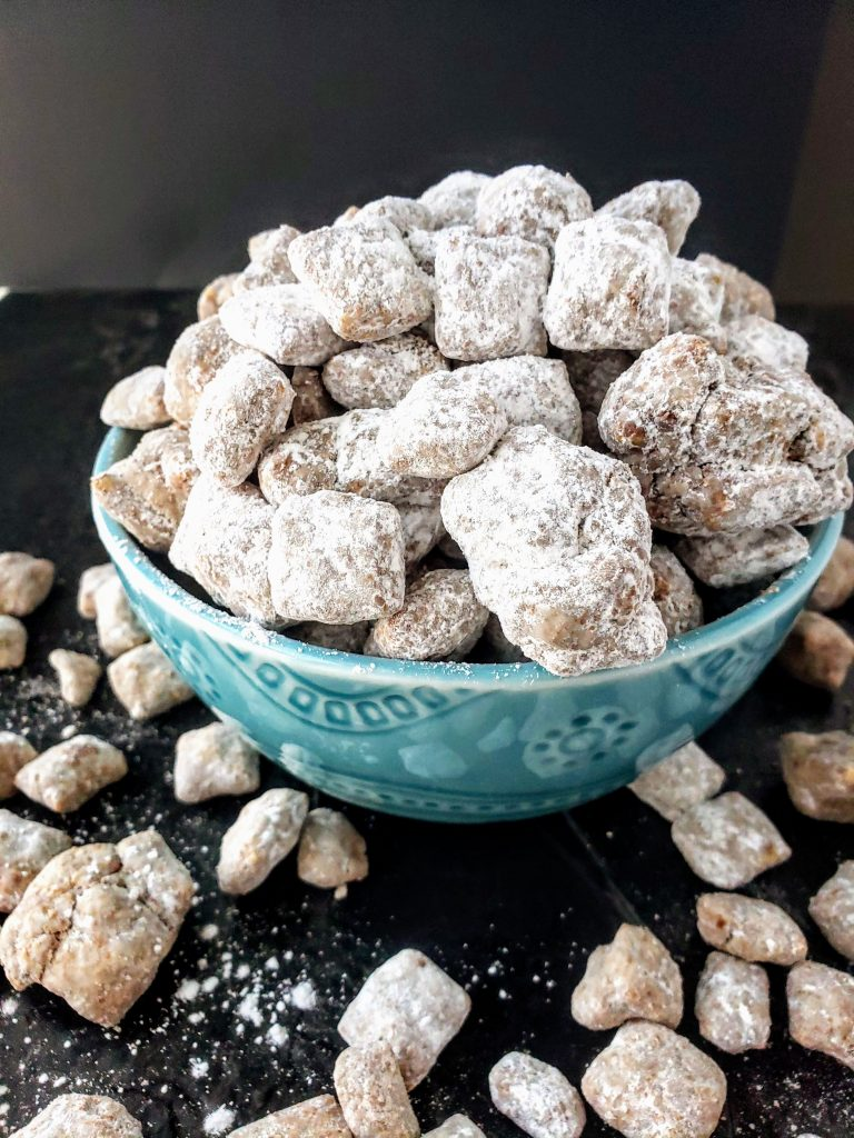 healthy-ish puppy chow in a blue bowl with puppy chow scattered around it