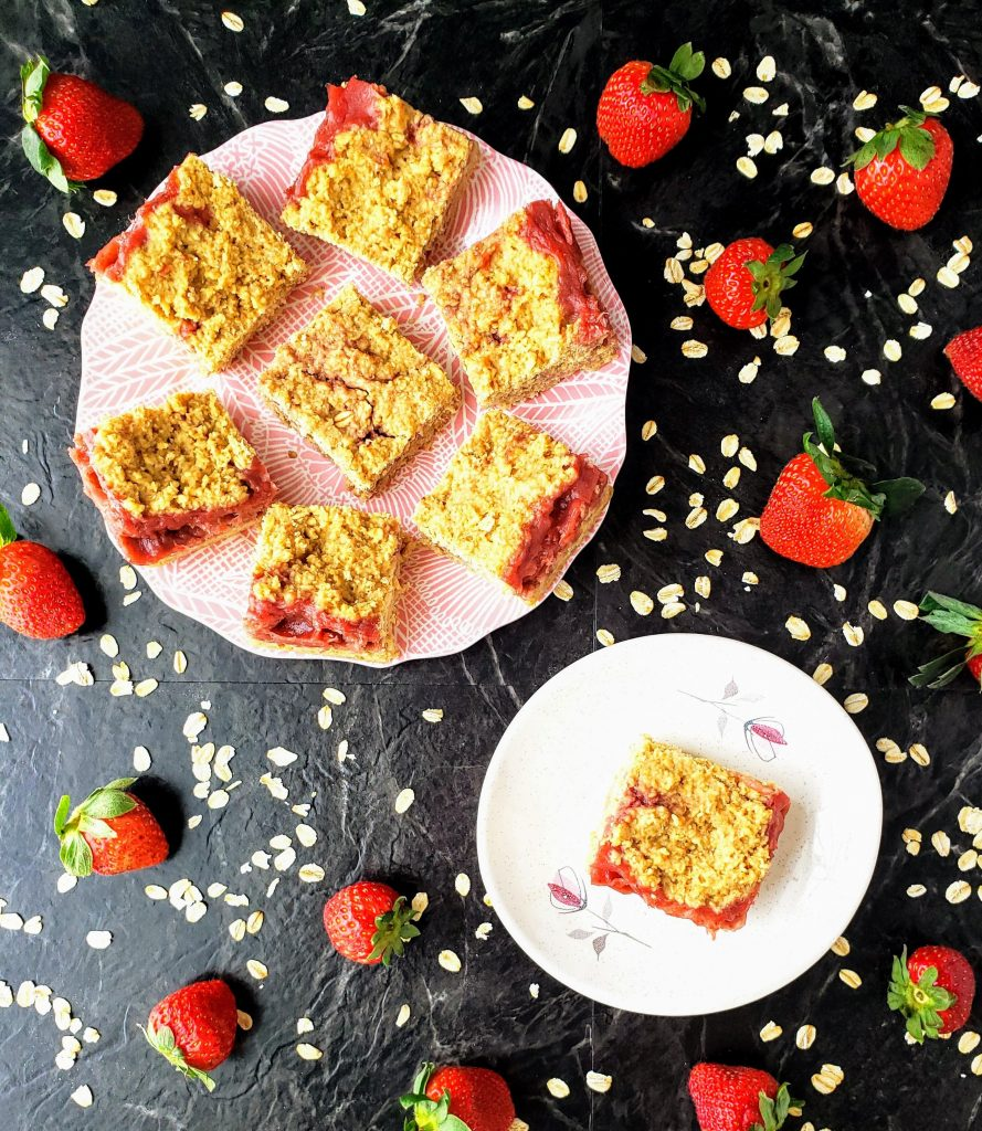 two plates of strawberry oat bars surrounded by fresh strawberries