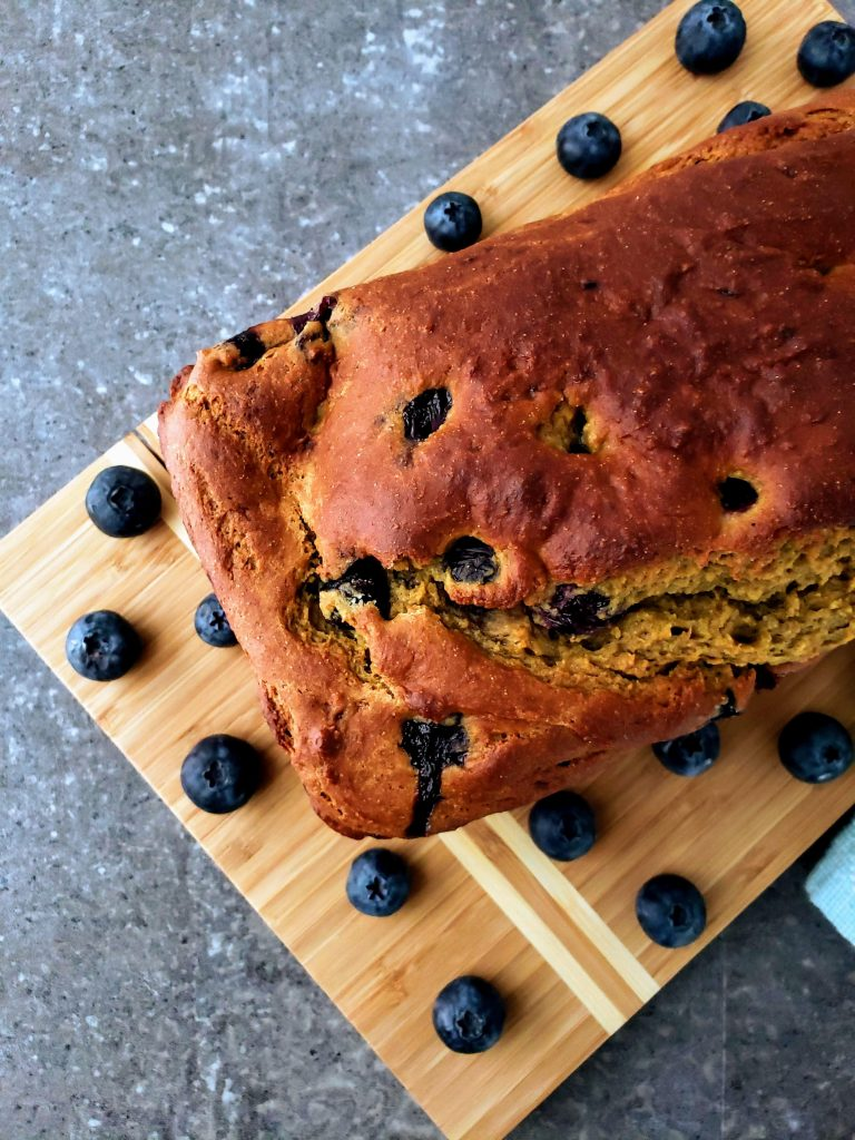 loaf of blueberry banana bread on a cutting board surrounded by blueberries