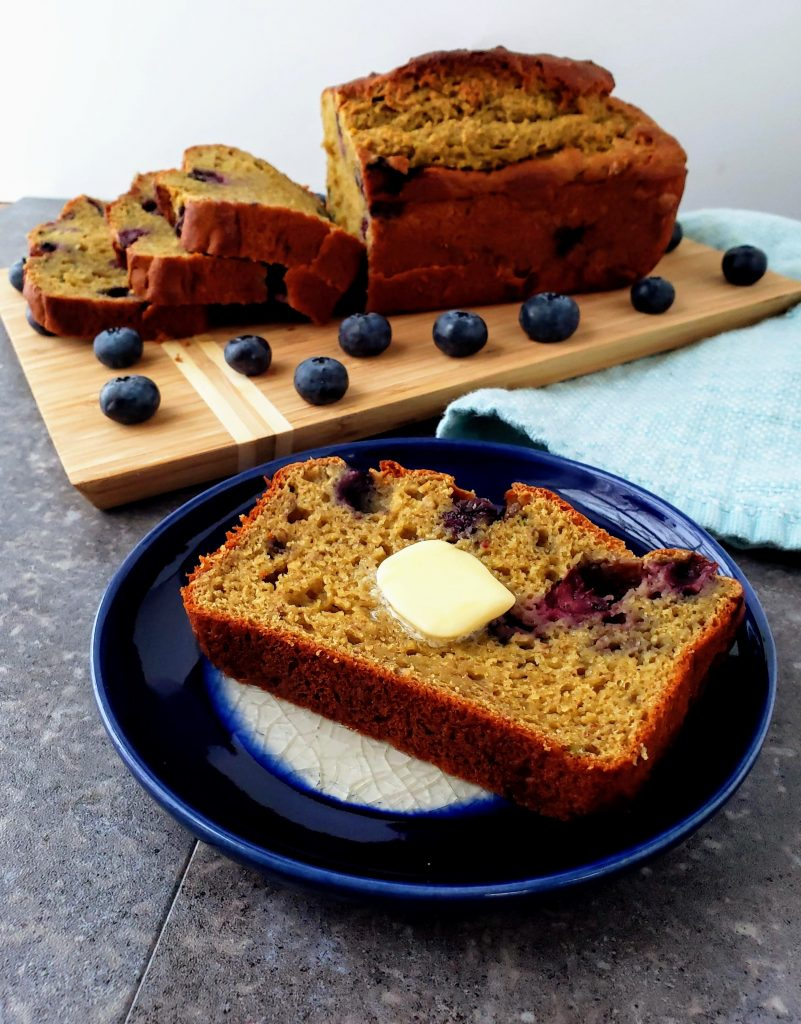 blueberry banana bread slice on a plate with a pat of butter melting on top