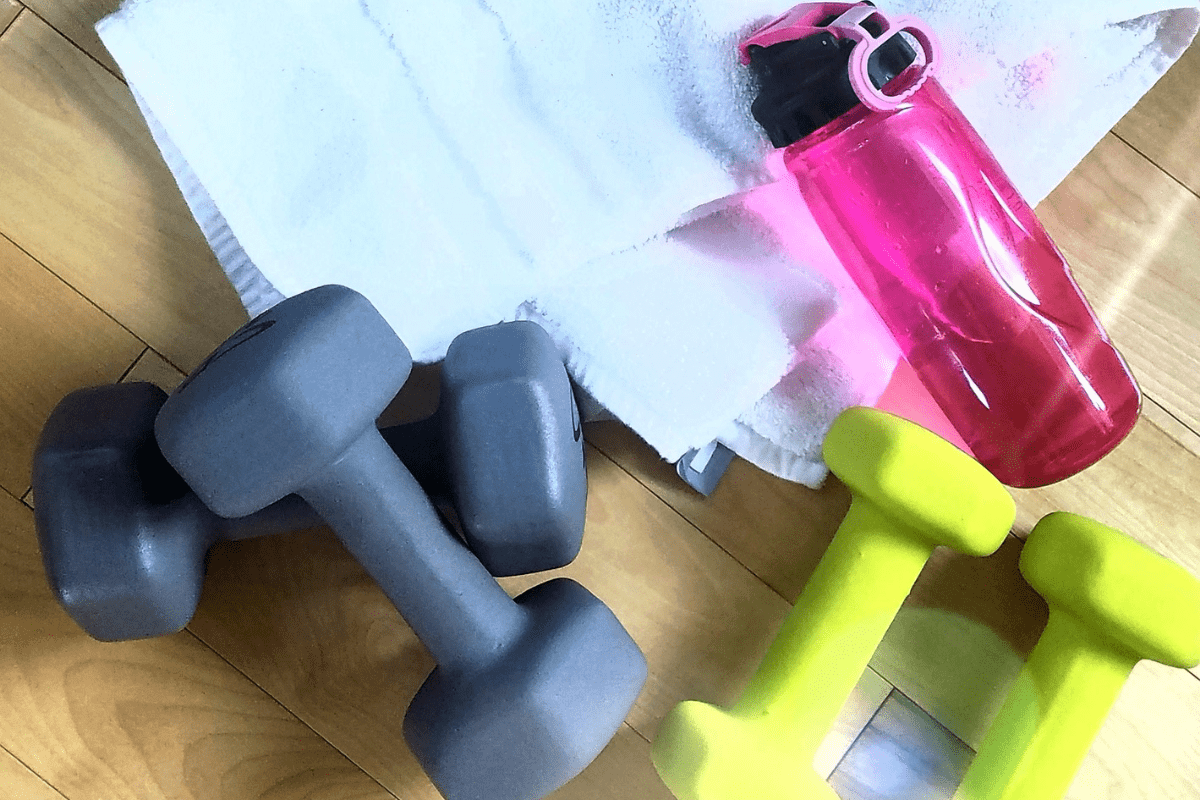 two sets of dumbbells on the floor with a pink water bottle on a white workout towel