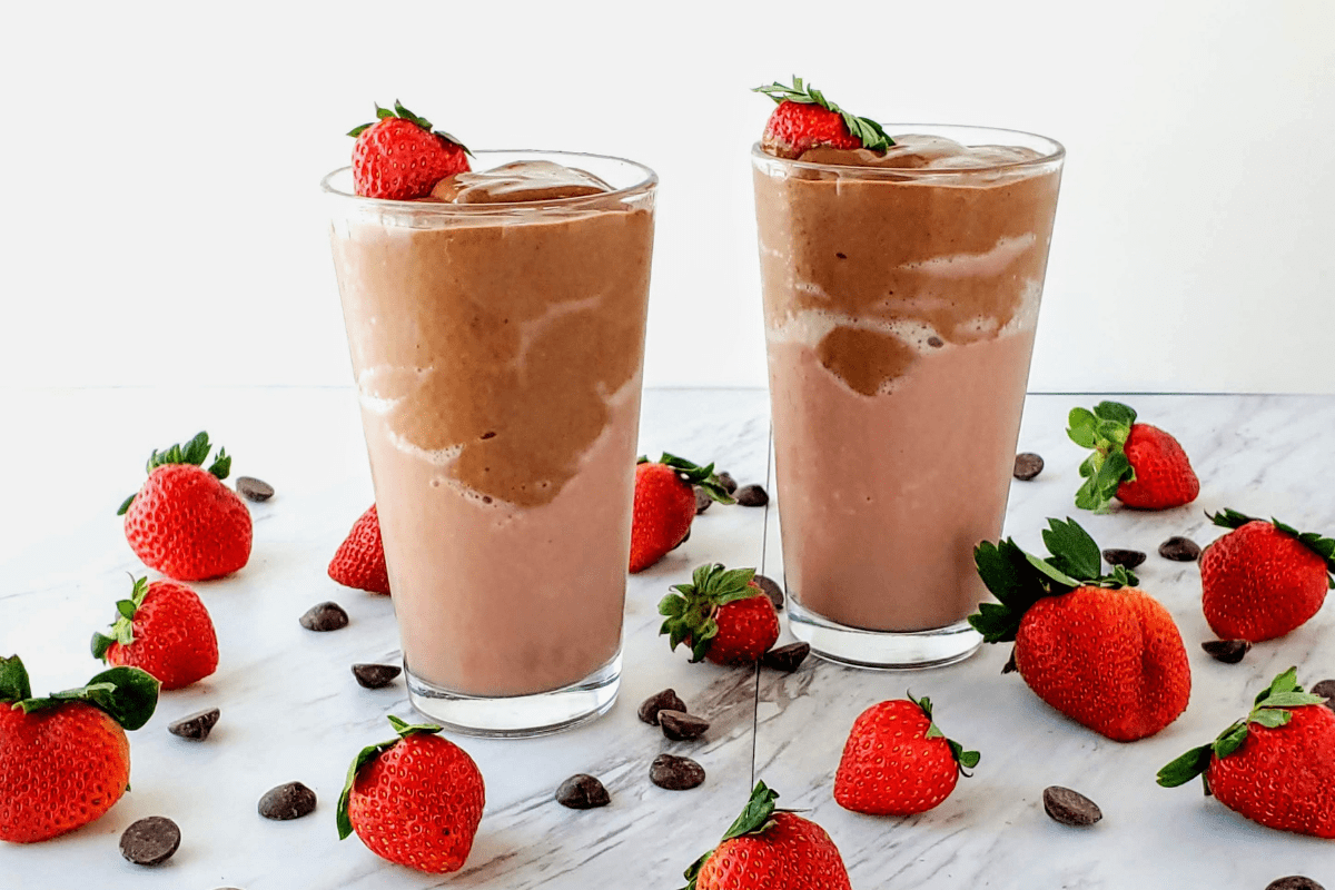 two glasses of chocolate covered strawberry smoothie surrounded by strawberries and chocolate chips