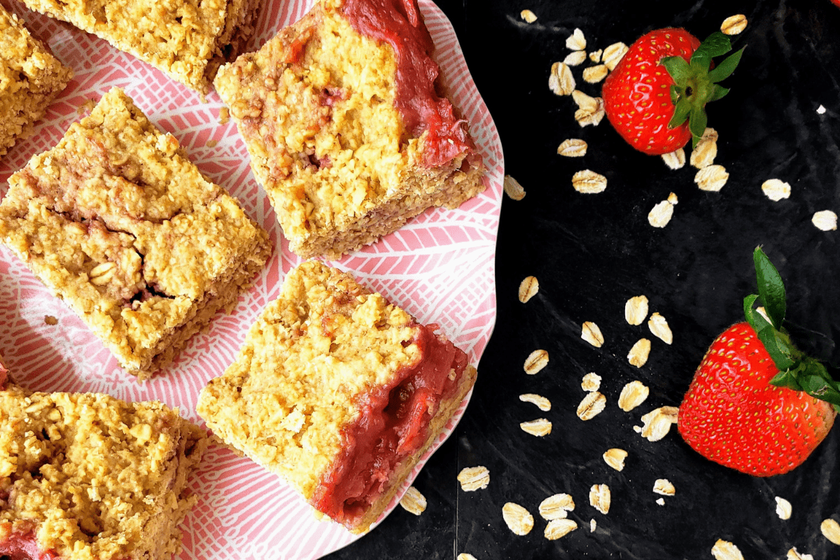plate of strawberry oat bars surrounded by fresh strawberries
