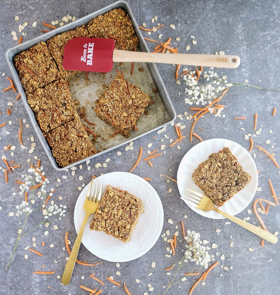 Carrot cake baked oatmeal on two white plates with gold forks and a pan of baked oatmeal with a red spatula in the pan.