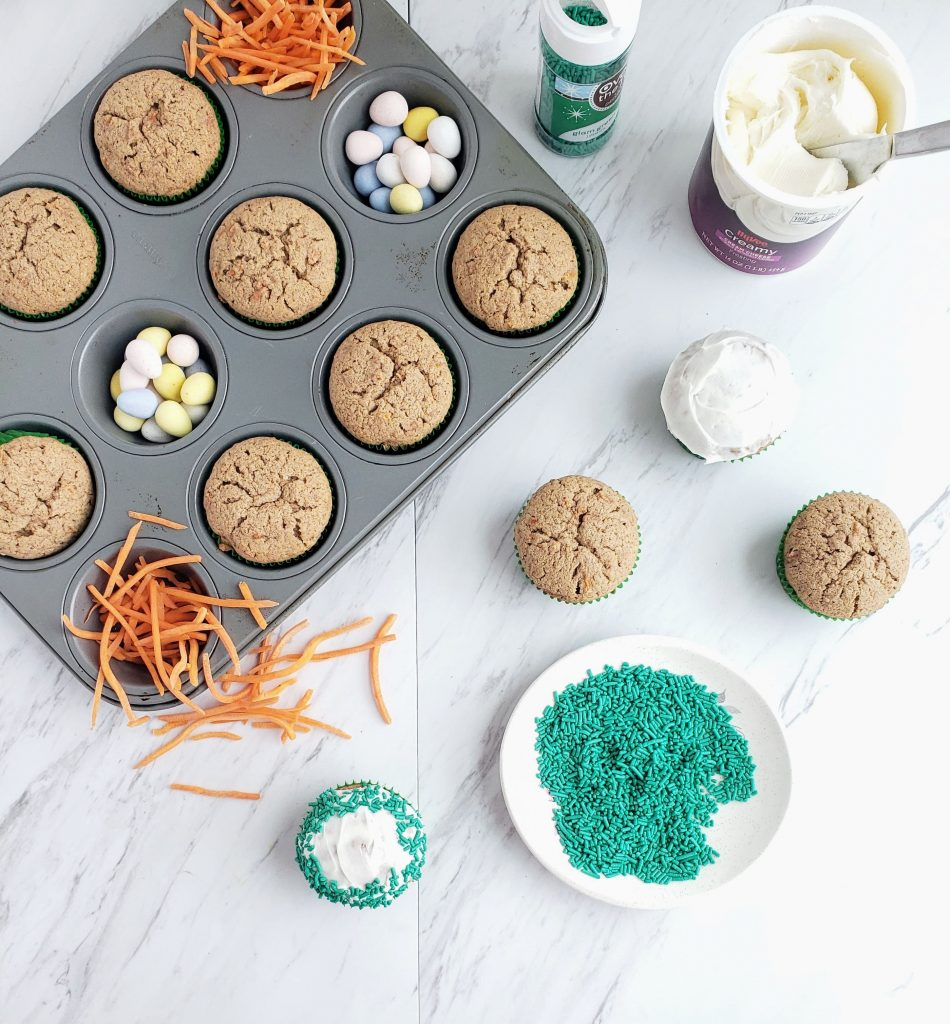 Carrot cake cupcakes in a muffin tin, a few being frosted, and green sprinkles on a plate