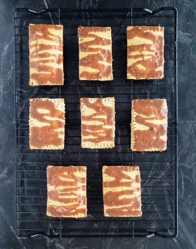 Frosted homemade toaster strudels on a black wire rack