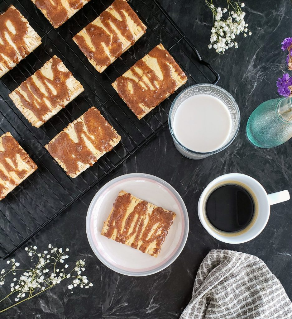Breakfast scene of homemade toaster strudels, coffee mug, glass of milk, and flowers