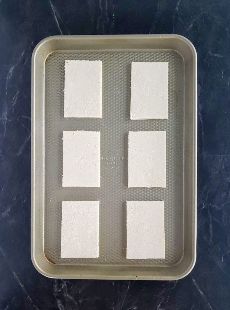 sheet pan with cut sheets of dough before filling