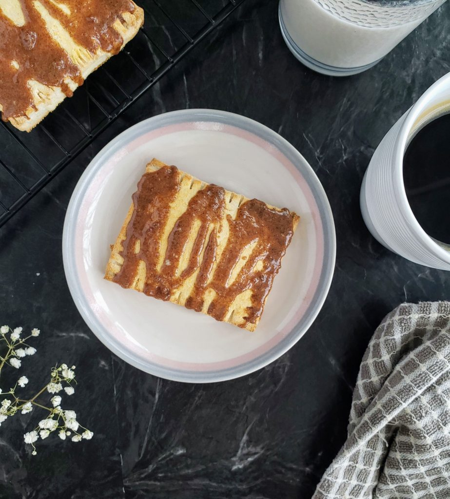 Top down image of homemade toaster strudel on a plate with a mug of coffee and glass of milk to the right