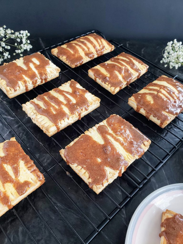 Homemade toaster strudels on a wire rack with white flowers in the background