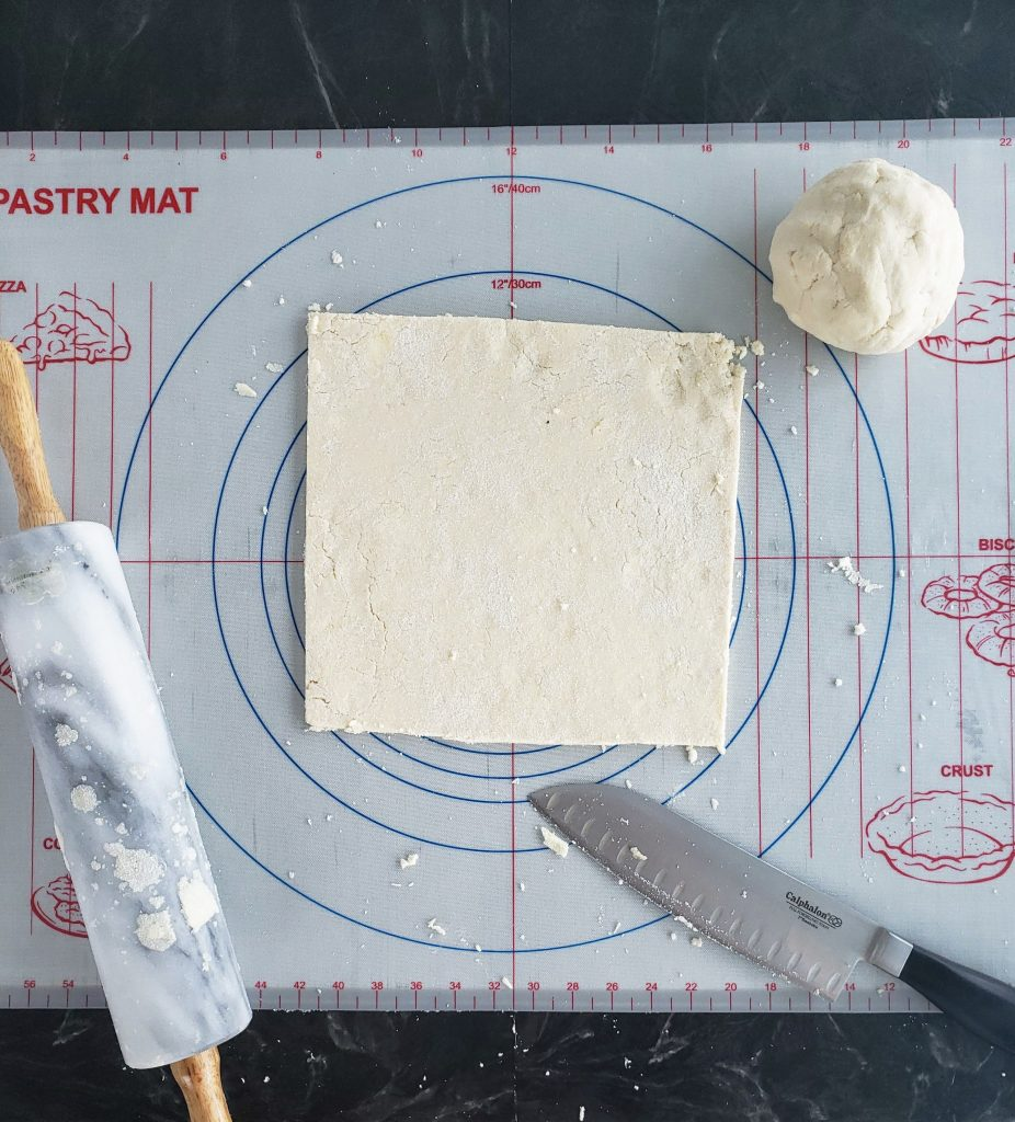 Homemade toaster strudel dough rolled out into a square with a rolling pin to the left and a knife on the lower right after cutting