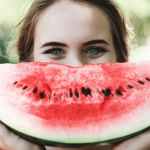 Girl holding half a cut watermelon to look like a smile