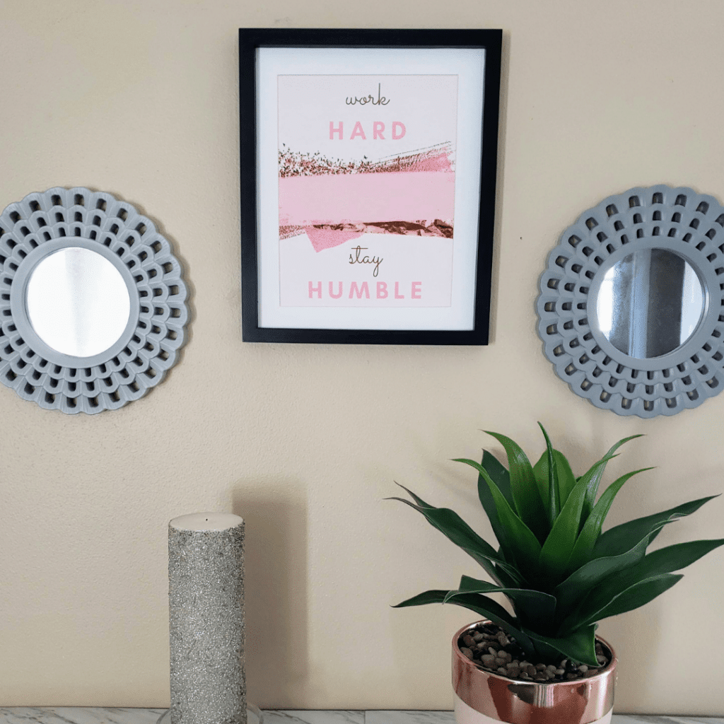 Home decor Wall art between two mirrors, above a plant and silver candle