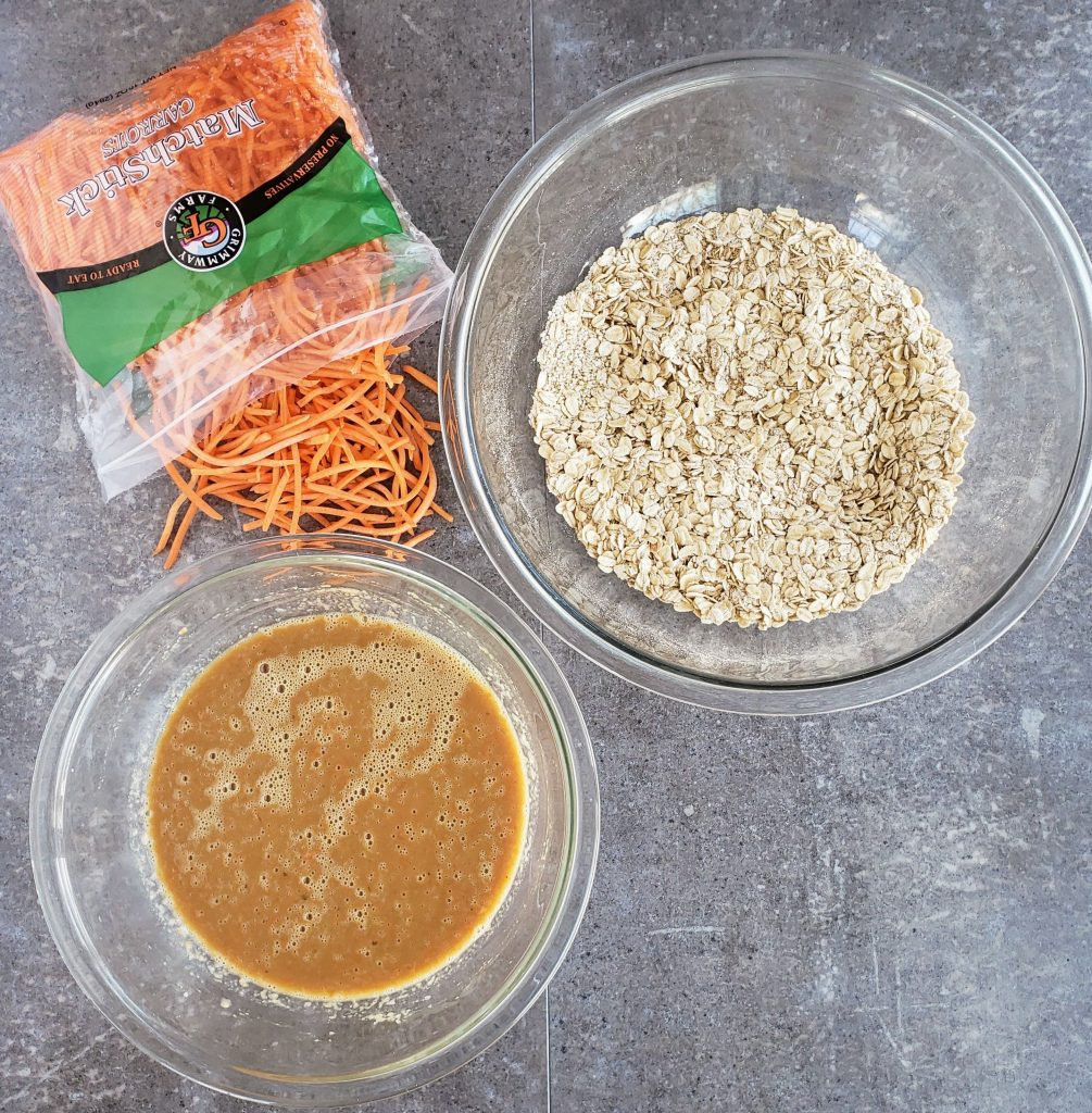large bowl of oats, bowl of wet ingredients to the left, and shredded carrots spilling out of a bag on the left.