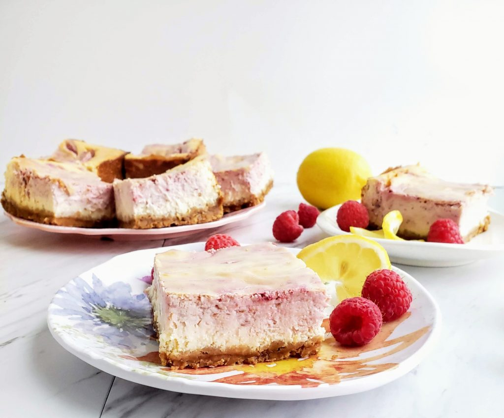 slices of lemon raspberry cheesecake on multiple plates
