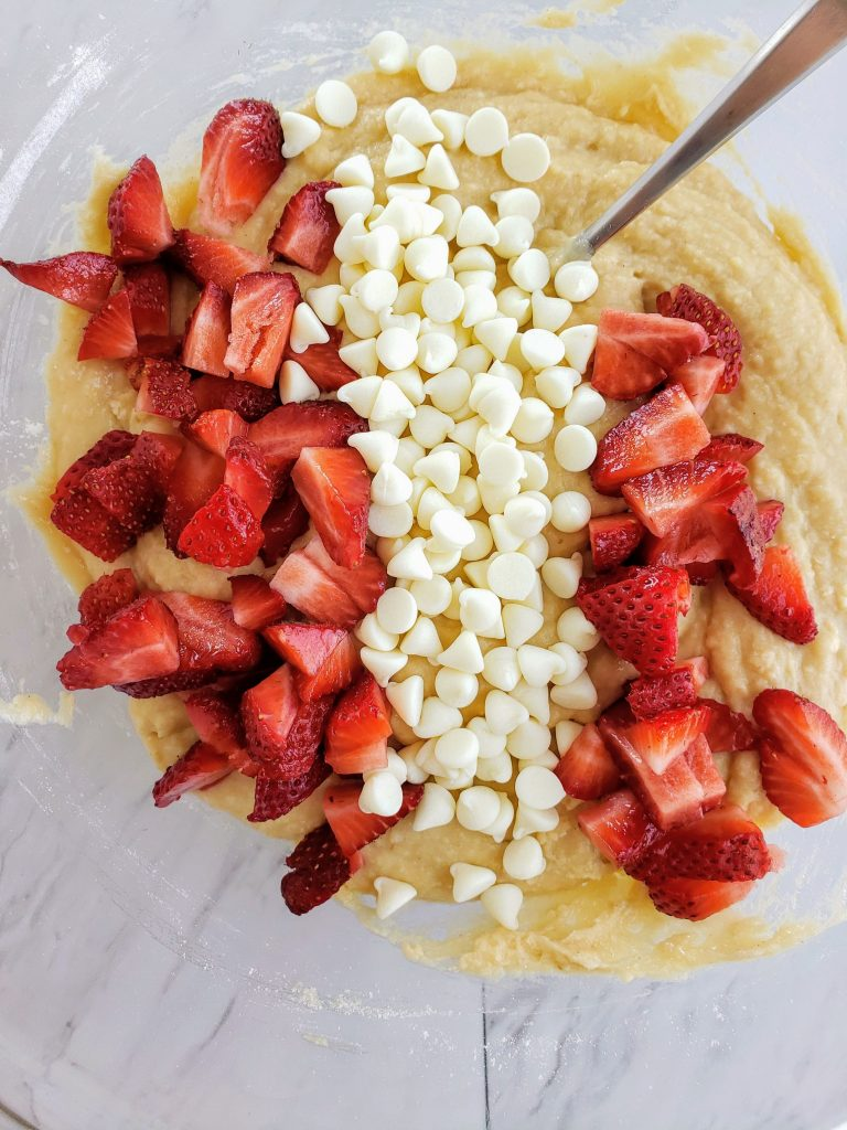 bowl of fresh strawberries, cake batter and white chocolate chips