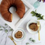 Two slices of coffee cake on plates, gold forks on the side, whole coffee cake on a white cake plate