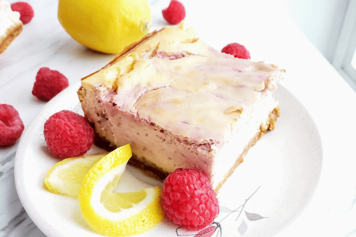 one slice of lemon raspberry cheesecake on a white plate, surrounded by raspberries and lemon slices