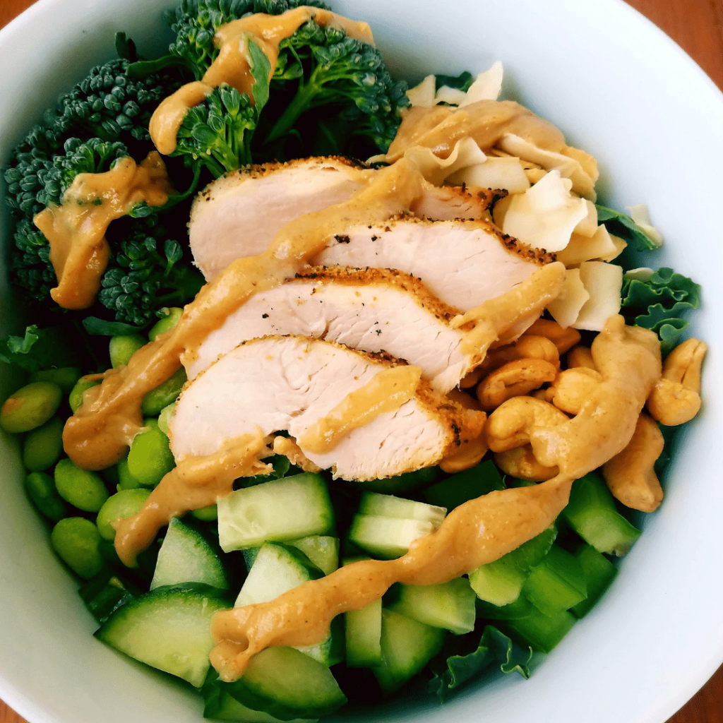 green salad with chicken and peanut sauce drizzled over the top