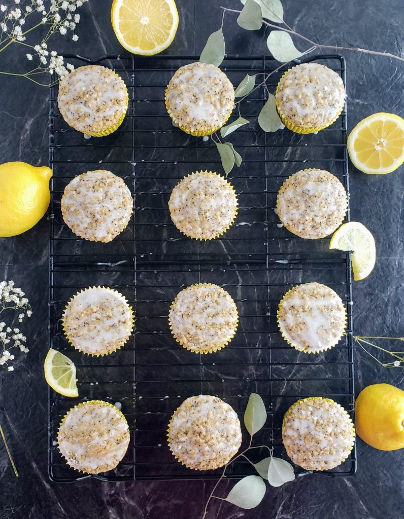 lemon poppyseed muffins on a baking rack surrounded by lemons and flowers