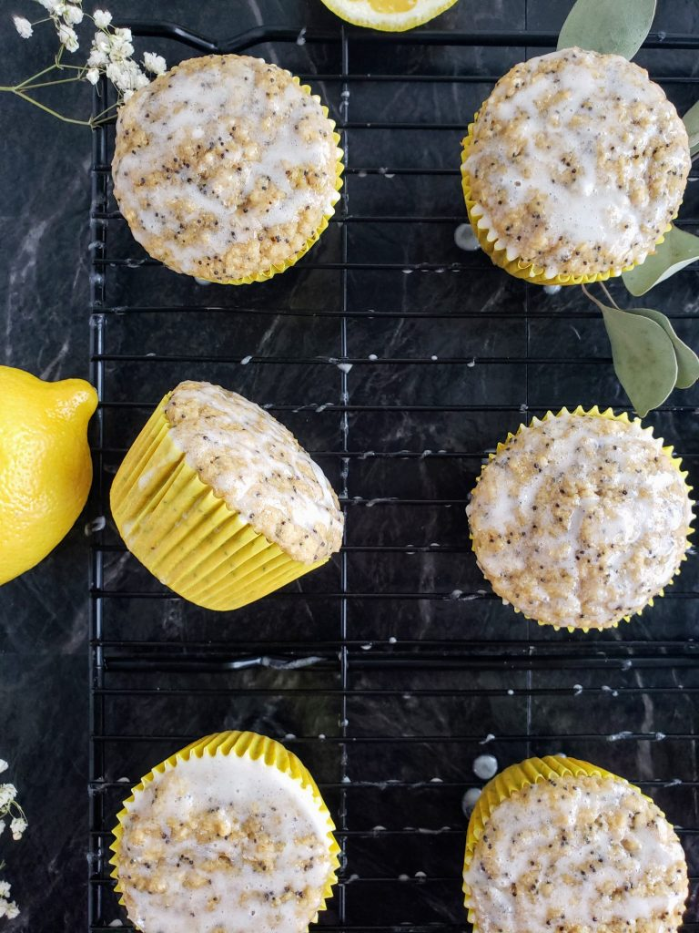 lemon poppyseed muffins, one turned on its side, on a baking rack