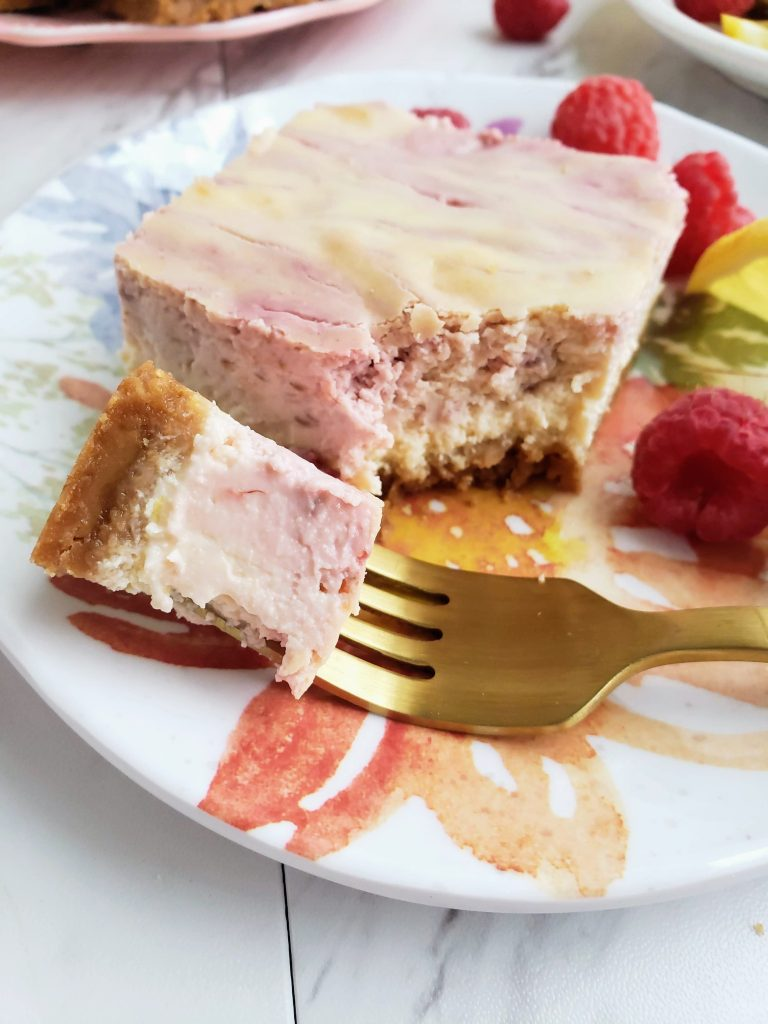 bite of lemon raspberry cheesecake on a gold fork