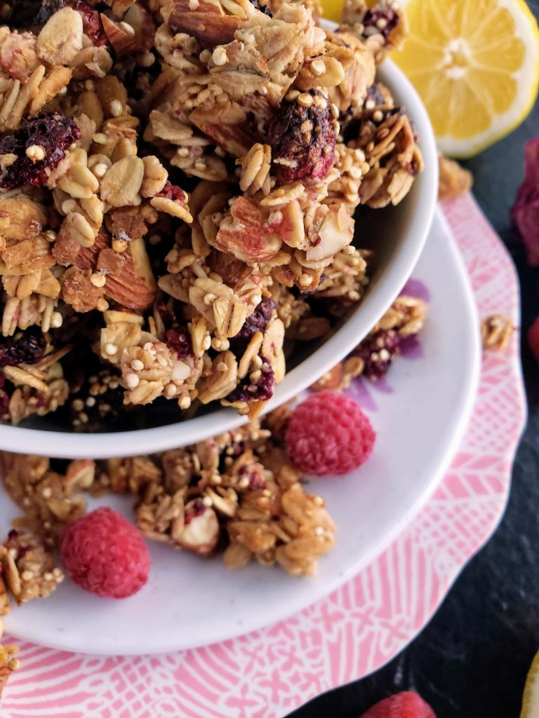 up close of a bowl of homemade granola sitting on top of two stacked plates