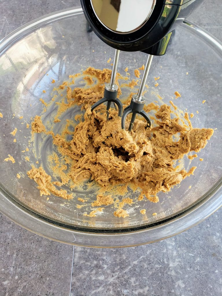 hand mixer in a mixing bowl mixing up no bake cookie dough batter