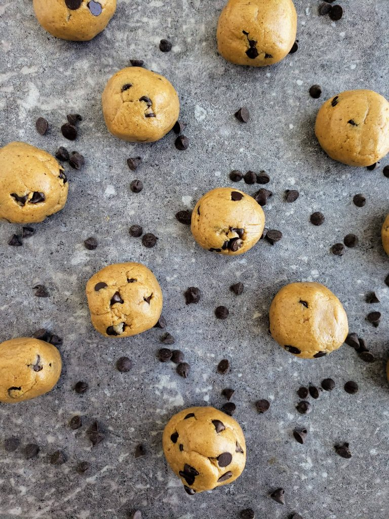 5 no bake cookie dough bites scattered around with chocolate chips surrounding them