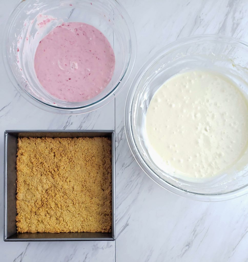 One bowl of plain cheesecake, one bowl of raspberry cheesecake, one baked cookie crust in a pan