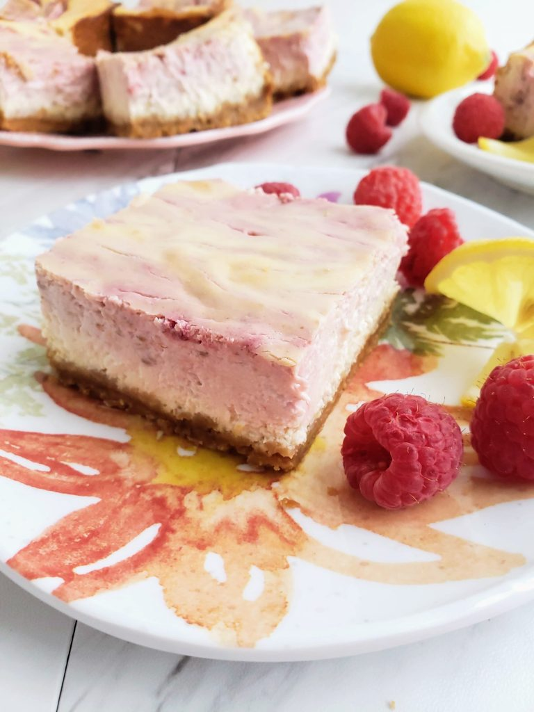 slice of lemon raspberry cheesecake on a floral plate