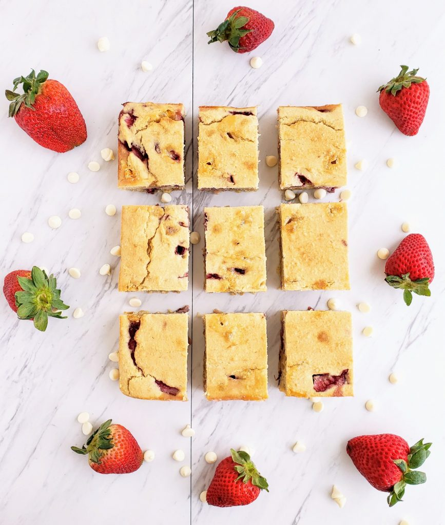 Slices of strawberry cake surrounded by fresh strawberries