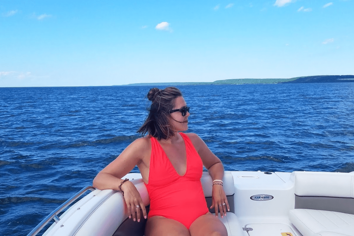 woman sitting on a boat in a one piece red swimming suit