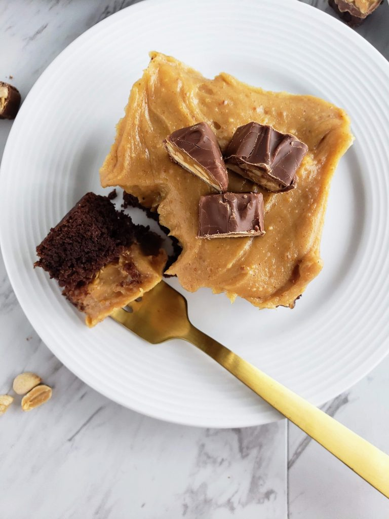 snickers cake slice on a white plate with a bite taken out on a gold fork