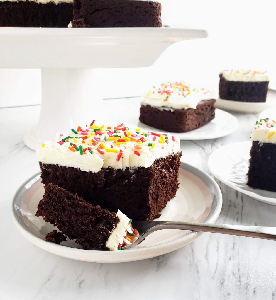 slices of gluten free chocolate cake on white plates. One slice with a forkful taken out