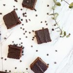 sweet potato brownies on a white marble surface surrounded by mini chocolate chips