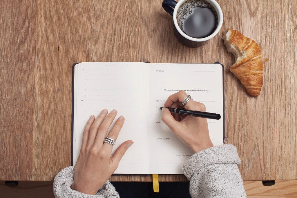 woman journaling with a coffee and half eaten pastry next to her