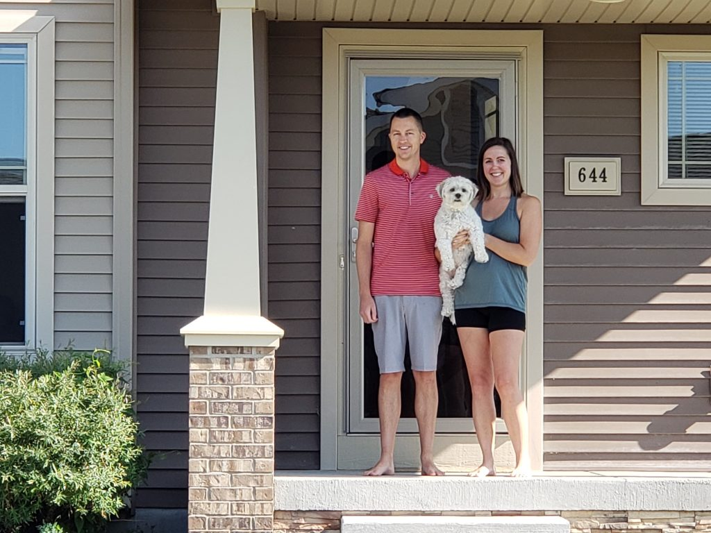 man, woman and dog standing in front of home