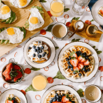 breakfast scene laid out on a table with waffles, eggs, toast