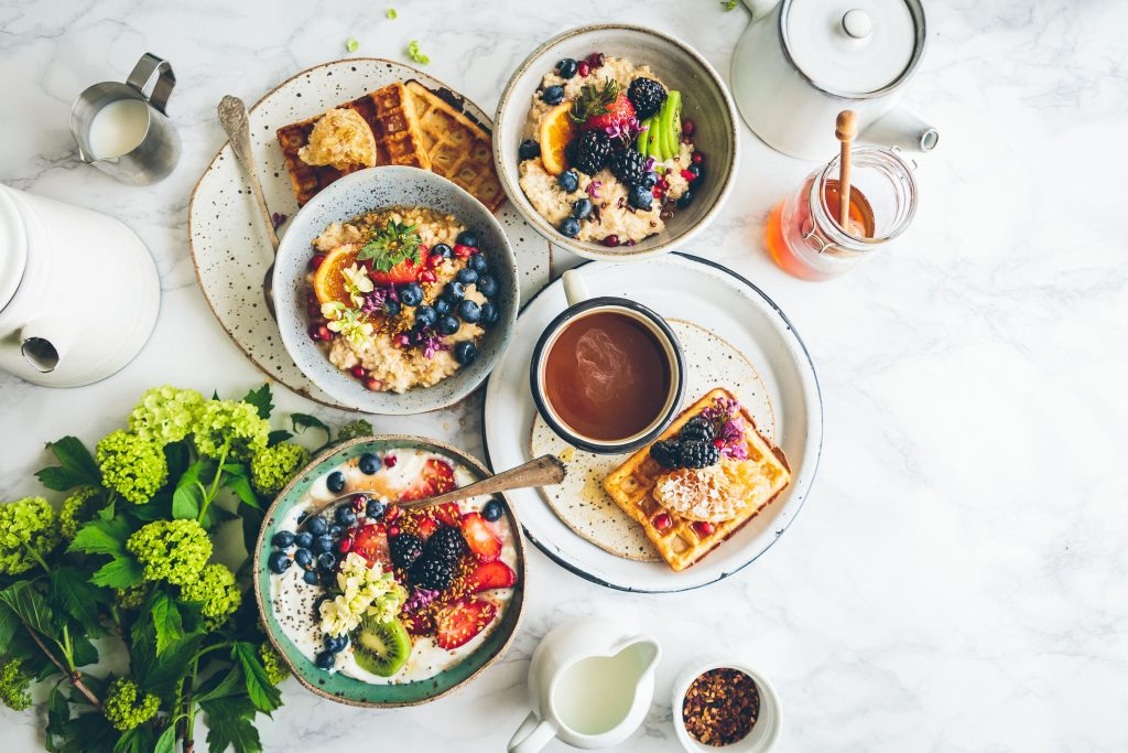 breakfast scene with waffles and fresh fruit and flowers